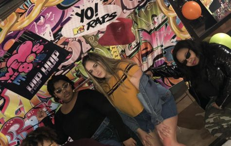From left to right: Jada Barnes, Kandi Holmes, Emily Bizub, and Jamierra Givens are slaying in their 90s fits in front of the retro backdrop.