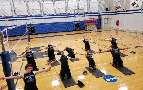 Men's volleyball players using some yoga technique to prepare for play.