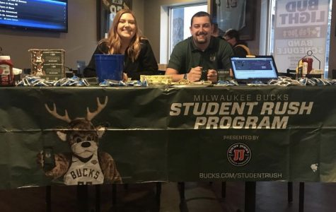 Gracie Thies (left) and Tyler VanRossum (right) wait for students to opt-in  to the Student Rush Program at Fat Joe's Bar and Grill.