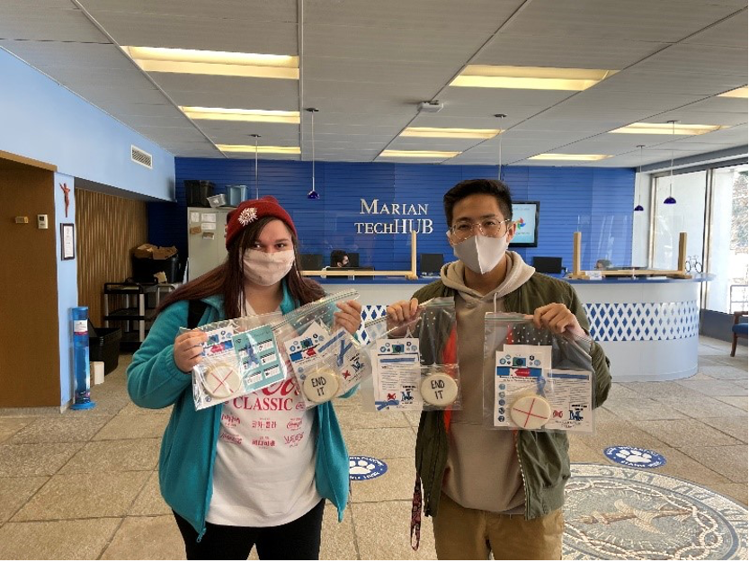 McKenna Hron and Martin Vu show the small packages given out to Marian University students to spread.